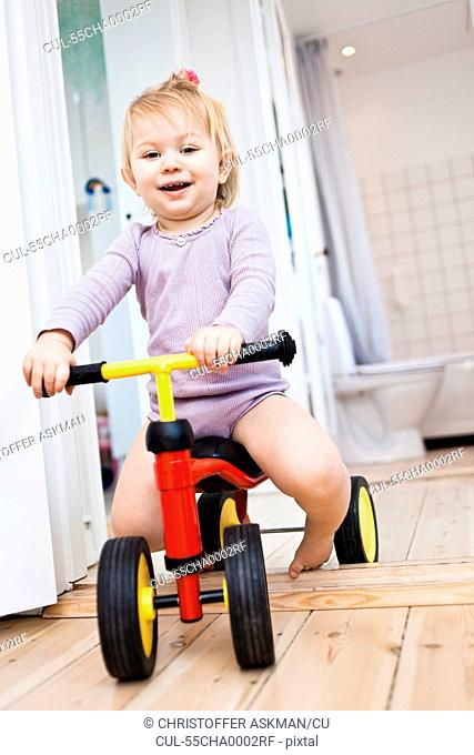 Toddler girl playing on tricycle