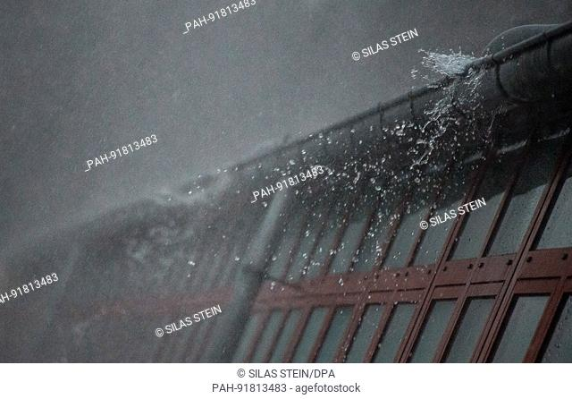 dpatop - Rainwater runs along a rain gutter due to heavy rainfall in Hanover, Germany, 22 June 2017. Photo: Silas Stein/dpa | usage worldwide