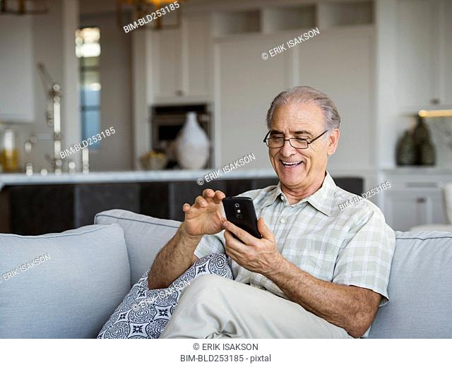 Caucasian man sitting on sofa texting on cell phone