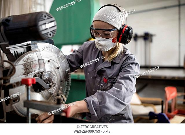 Woman wearing earmuffs and dust mask working on machine