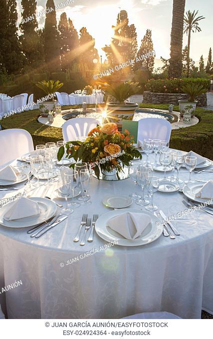 Garden table setting at wedding reception under sunset sun rays