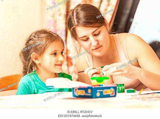 Mother helping daughter painting easter egg