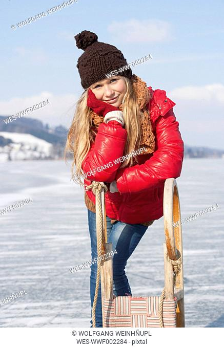 Austria, Teenage girl leaning on sleigh, smiling, portrait