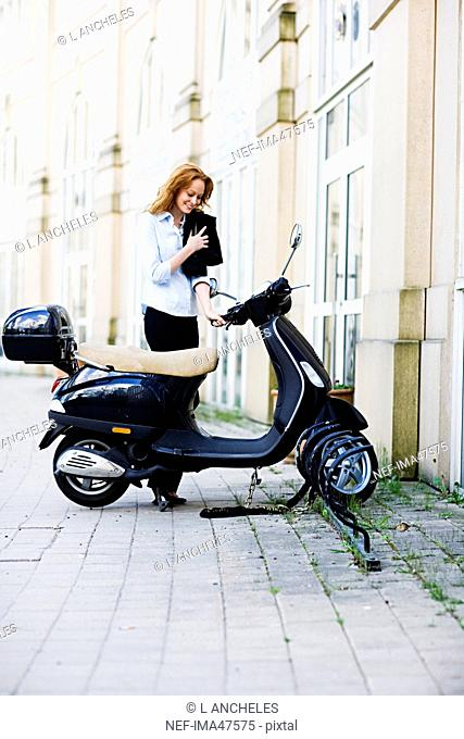 A woman standing on a street next to a motor scooter, Stockholm, Sweden