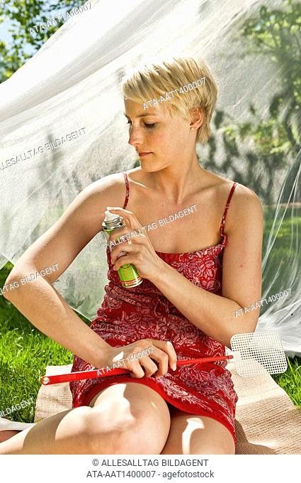 Woman using bug repellant