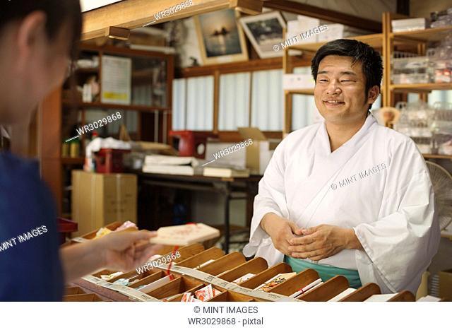 Salesman wearing white kimono at Shinto Sakurai Shrine, Fukuoka, Japan