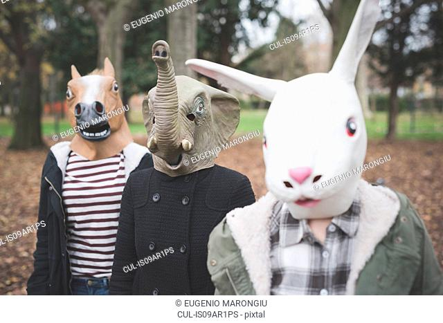 Three sisters wearing animal masks posing in park
