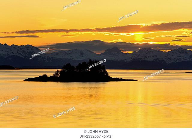 Sunset over favorite channel in inside passage with chilkat mountains and lynn canal in the distance;Alaska united states of america