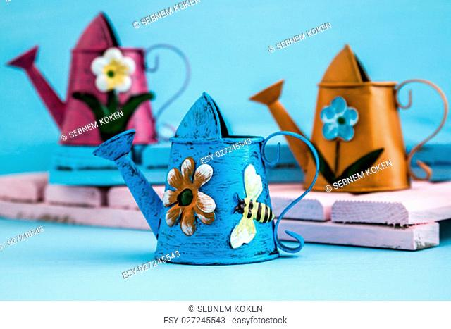 Colorful metallic watering cans on blue wooden background