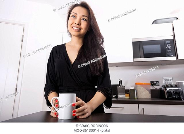 Thoughtful young woman having coffee in kitchen