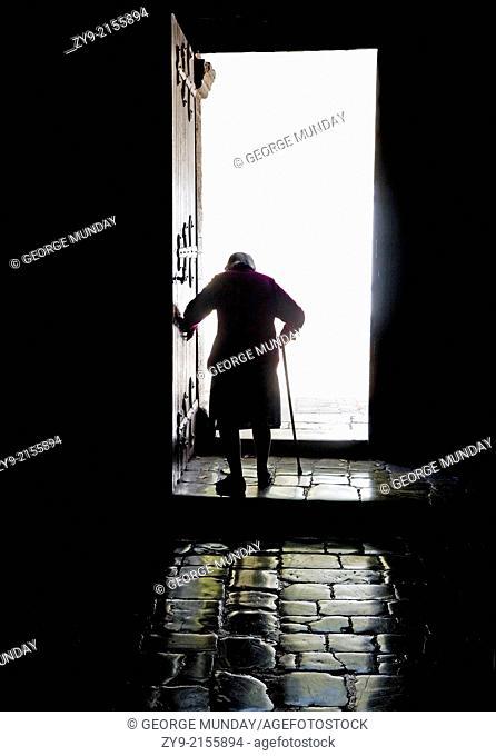 Old Lady leaving the abbey, St Guilhem le Desert, Languedoc-Roussillon, France
