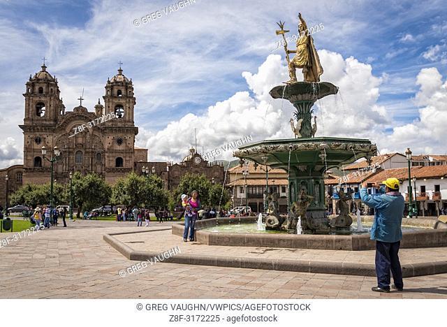 Visitors taking photo at fountain in Plaza de Armas with La Compañia church in background; Cusco. Peru