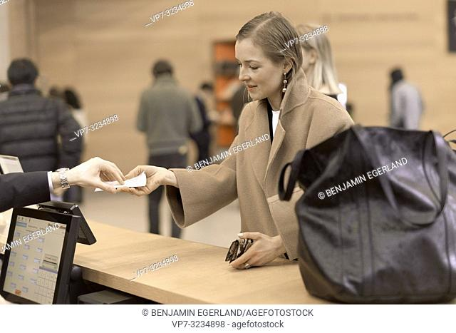 fashionable woman paying ticket entrance at reception of museum, in Munich, Germany