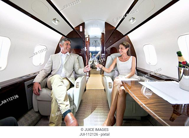 Smiling couple making a toast with champagne in private jet