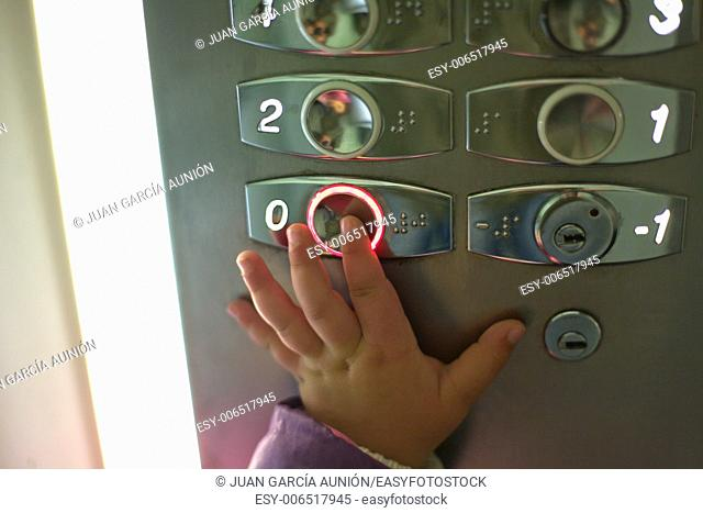 Hand of a toddler in elevator or lift pressing the button to get the ground floor.Closeup