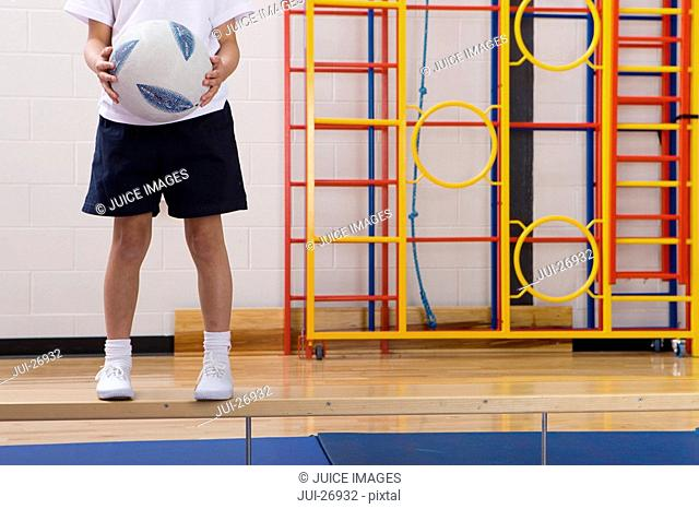 School boy standing on bench and holding ball in school gymnasium