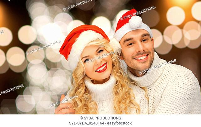 happy couple in santa hats over christmas lights