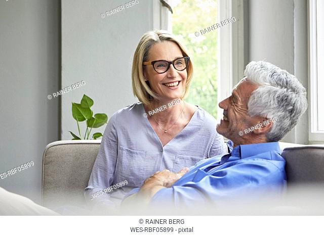 Happy mature couple on couch at home