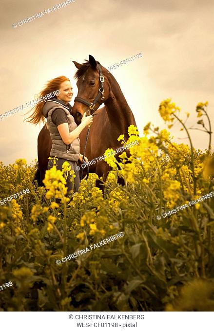 Portrait of happy young woman with her horse in a rape field