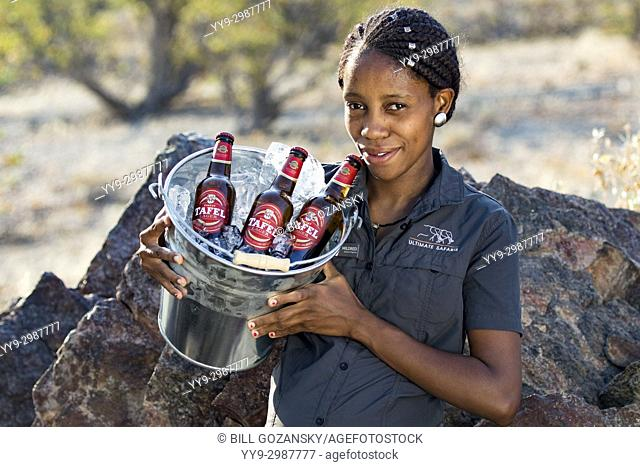Lodge staff carrying bucket of beer - Huab Under Canvas, Damaraland, Namibia, Africa