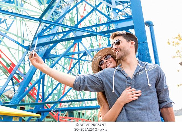 Couple at fairground using smartphone to take selfie, Coney island, Brooklyn, New York, USA