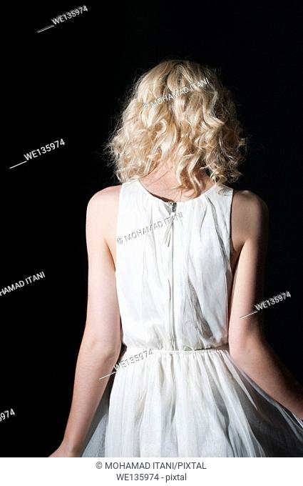 Rear view of a young woman in white dress
