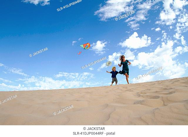 Mother and son flying kite on beach