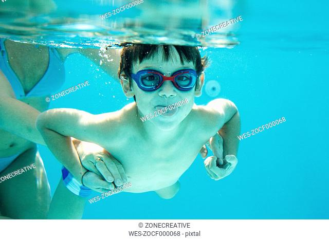 Young boy diving, mother is helping, sticking out tongue, under water, swimming pool