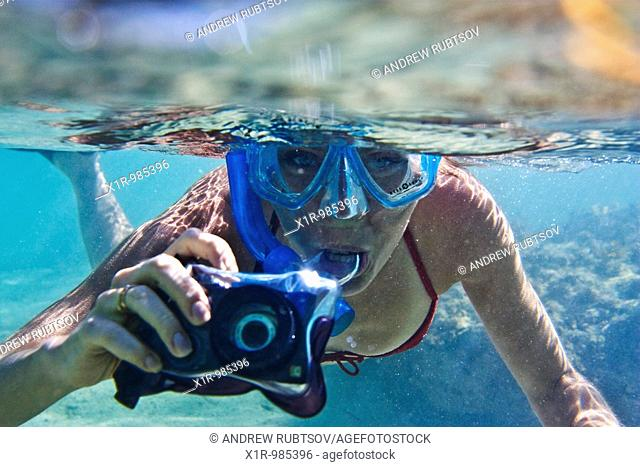 Young woman snorkeling and taking pictures underwater