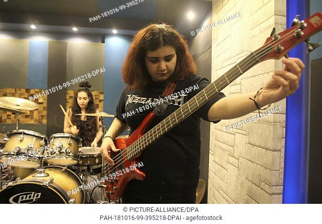 "26 September 2018, Lebanon, Antelias: Alma Doumiani (R), bass guitarist of Lebanese all-female heavy metal band """"Slaves to Sirens"""" adjusts her guitar chords"