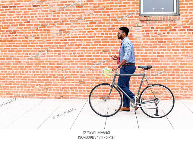 Young man walking with bicycle, side view