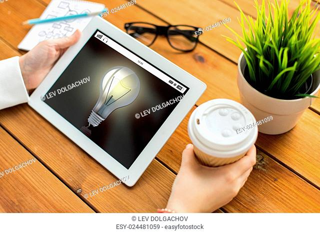 business, education, technology, people and inspiration concept - close up of woman with light bulb on tablet pc computer screen and coffee cup on wooden table