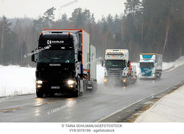Two special transport semi trucks and a cargo semi trailer move along highway in South of Finland in challenging winter weather conditions
