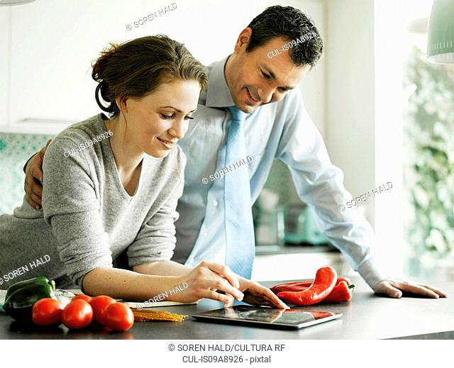Businessman and wife using digital tablet in kitchen
