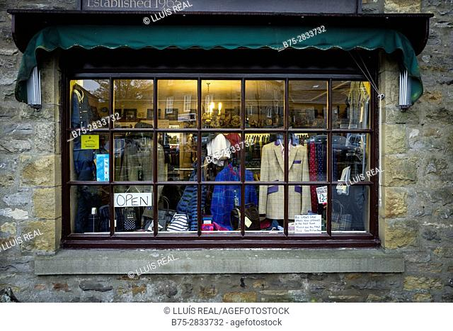 "Shop window of a traditional English clothing store with the ""OPEN"" sign. Grassington, Yorkshire Dales, North Yorkshire, Skipton, UK"