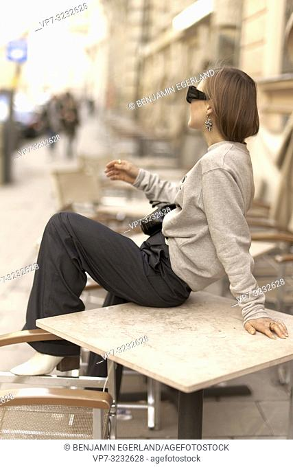 stylish blogger woman sitting on table of street café outdoors, streetstyle, in Munich, Bavaria, Germany