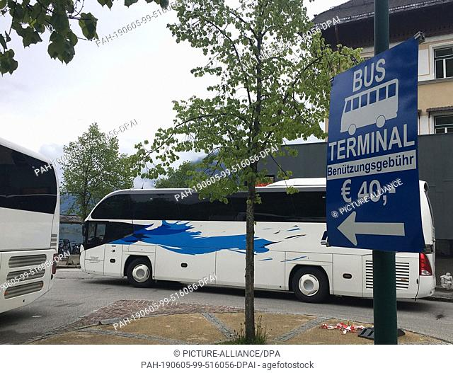 16 May 2019, Austria, Hallstatt: Buses are parked on the lakeside promenade in a car park where tourists get off and on. The bus companies have to pay 40 euros...