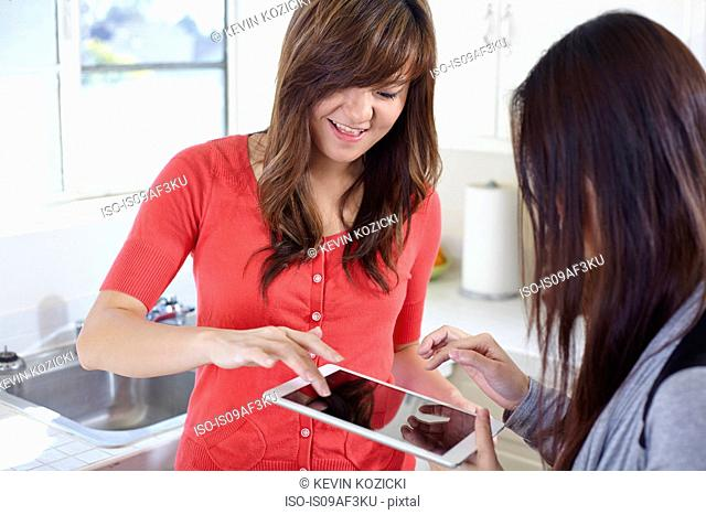 Two young women in kitchen playing game on digital tablet