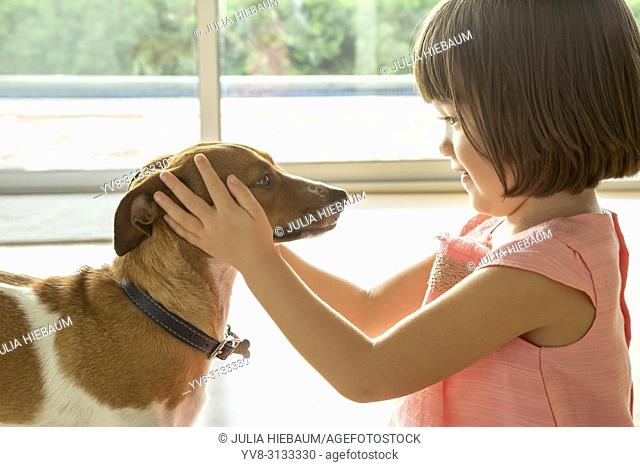 A toddler girl holding her puppy's head in her hands