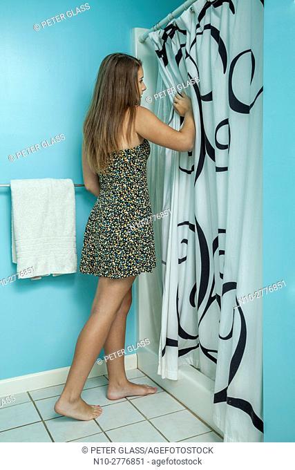 Teenage girl looking into her bathroom shower