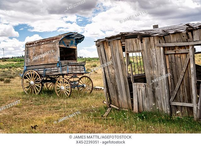 An old west sheriff's wagon sits on the lonesome frontier prarie as storm clouds gather in the distance