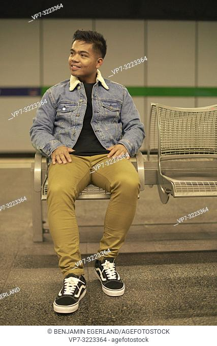 young man sitting on bench in underground train station, public transportation, in Munich, Germany