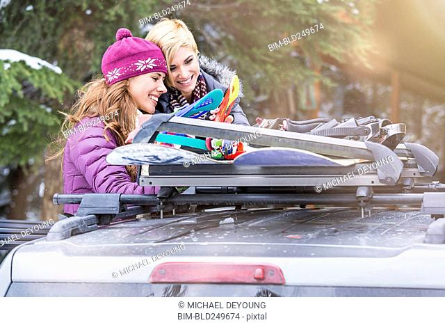 Caucasian women checking snowboards in car roof rack