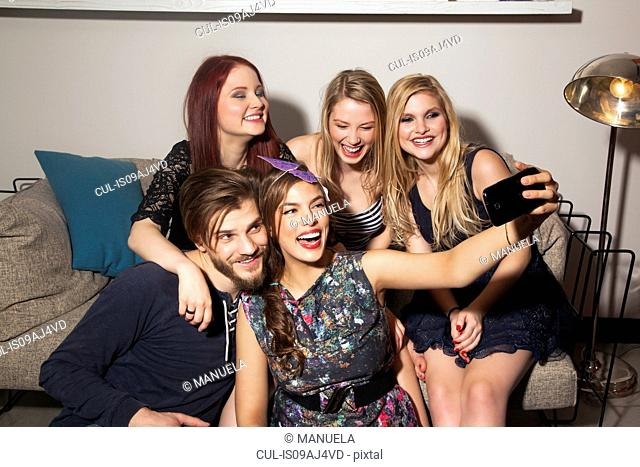 Friends taking selfie on sofa