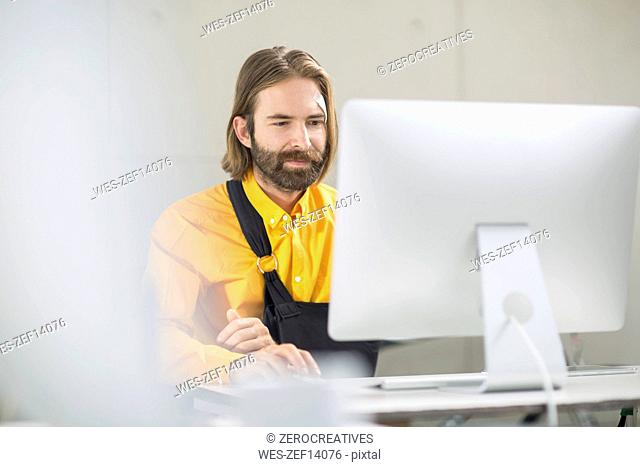 Employee focusing on his work wearing a sling