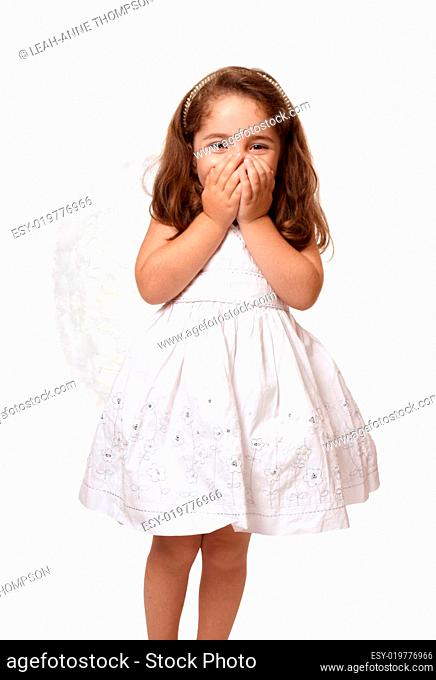 Little angel girl with hands covering her mouth