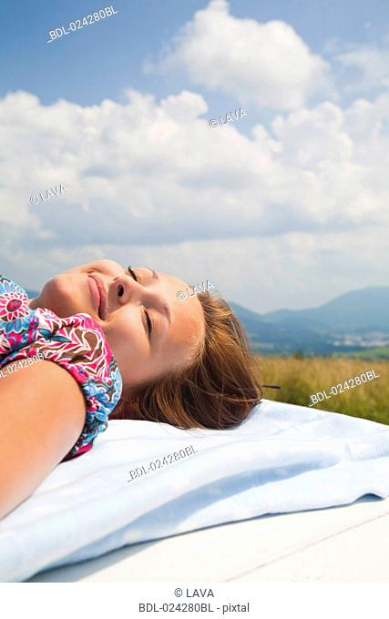 young woman dozing on roof of car