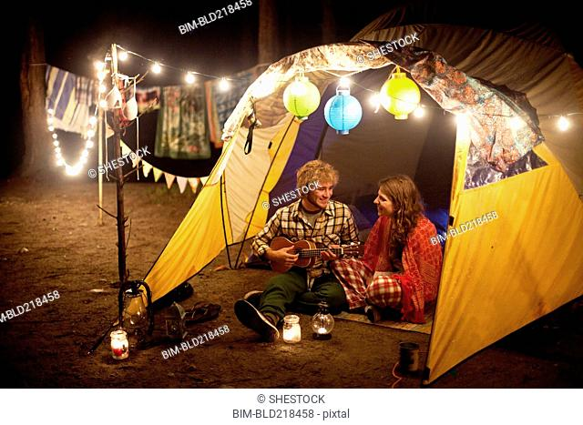 Couple playing music in camping tent at night