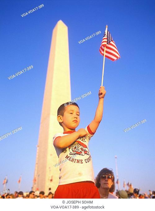 Child waving a miniature American flag at the Washington National Monument, Washington D.C