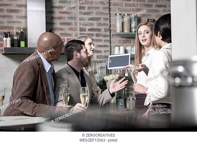 Friends with champagne glasses and tablet at home
